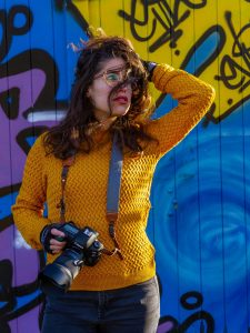 Colourful photo of Annemarie Sint Jago holding her DSLR camera, in front of a wall with graffiti