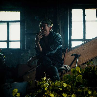 Old man sitting in a dark room, staring, smoking a cigarette